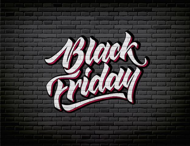 Czarny piątek napis ręcznie rysowane tuszem pędzla na tle czarnej cegły ściany