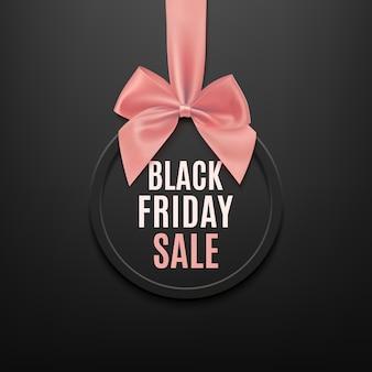 Czarny piątek okrągły baner z różową wstążką i kokardą, na czarnym tle. szablon broszury lub banera.