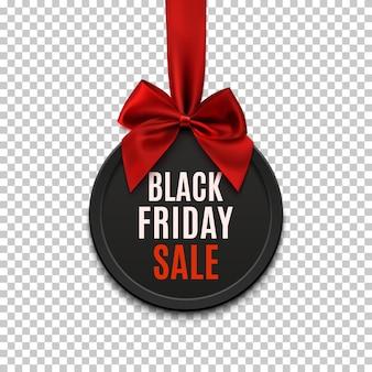 Czarny piątek sprzedaż okrągły baner z czerwoną wstążką i kokardą, na białym tle.