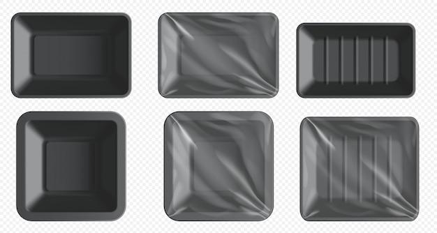 Czarny plastikowy pojemnik na żywność. taca styropianowa do mrożonek i świeżego mięsa, ryb, kurczaka. puste opakowanie żywności z przezroczystym opakowaniem na białym tle. szablon pustej tacy z tworzywa sztucznego na przezroczystym tle