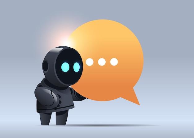 Czarny robot cyborg trzymający bańkę czatową komunikacja chatbot obsługa klienta technologia sztucznej inteligencji