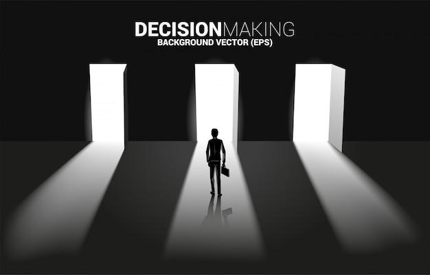 Czas podjąć decyzję w kierunku biznesowym. sylwetka biznesmen stoi wybierać drzwi wchodzić do