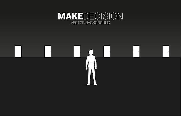 Czas podjąć decyzję w kierunku biznesowym. sylwetka biznesmen stojący, aby wybrać drzwi do wejścia