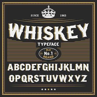 Czcionka etykiety whisky i przykładowy projekt etykiety. krój pisma w stylu vintage w czarno-złotych kolorach, edytowalny i warstwowy