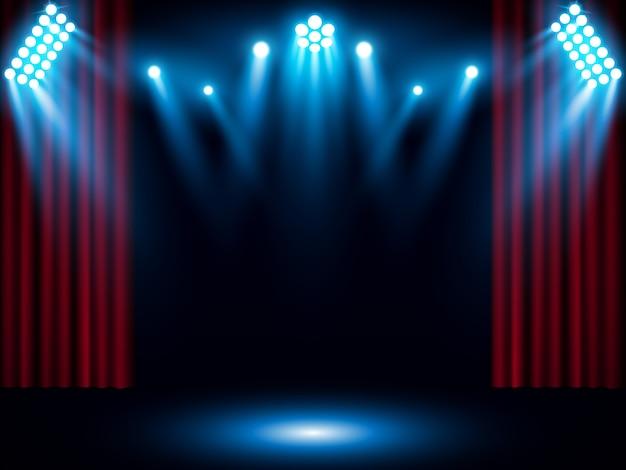 Czerwona kurtyna scenie z niebieskim reflektorem