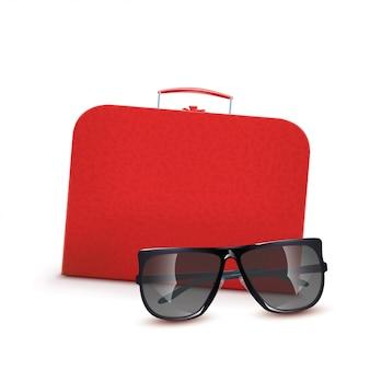 Czerwona walizka z okularami przeciwsłonecznymi