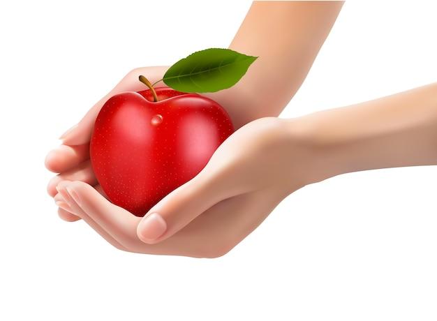 Czerwone dojrzałe jabłko w rękach na białym tle