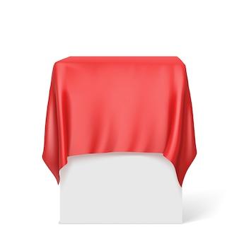 Czerwone szmatki na kwadratowym cokole na białym.
