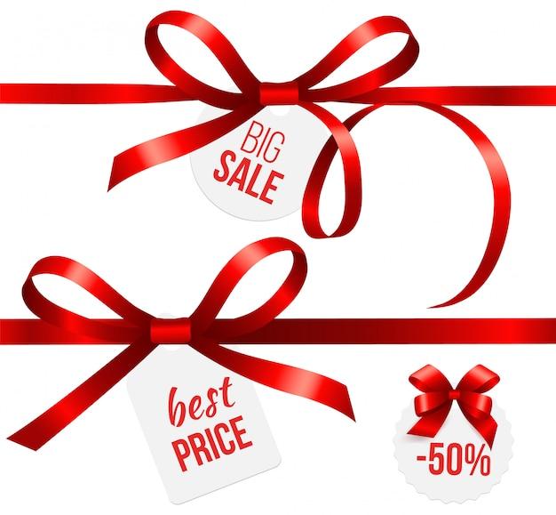 Czerwone wstążki. jedwabne kokardki z metkami sprzedażowymi. odznaki świąteczne zniżki na święta bożego narodzenia
