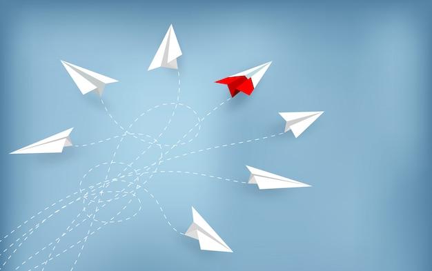 Czerwony papierowy samolot zmienia kierunek z białego. nowy pomysł.