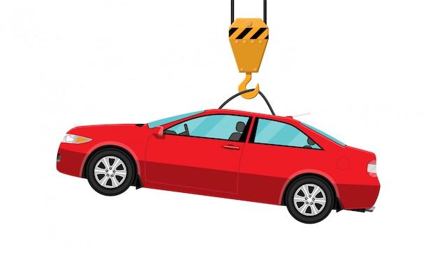 Czerwony samochód coupe wisi na haku dźwigu.