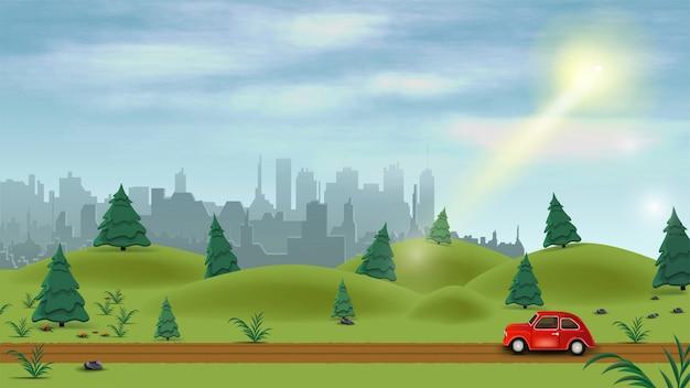 Czerwony samochód przejeżdża przez zielone pagórkowate pole pośrodku sosnowego lasu w jasny słoneczny dzień
