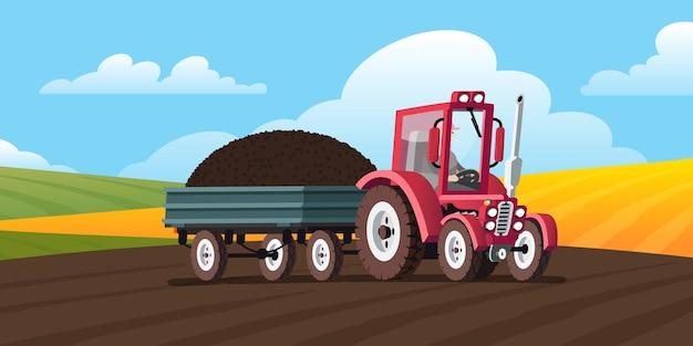 Czerwony traktor z przyczepą na polu pod górę