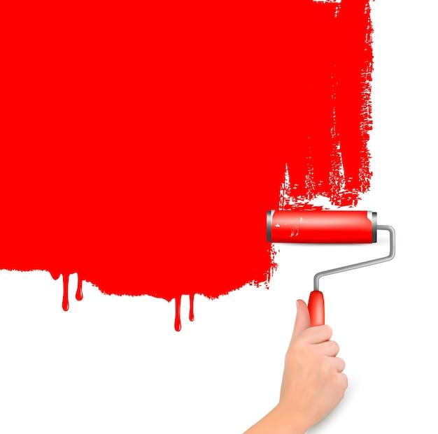 Czerwony wałek do malowania białej ściany.