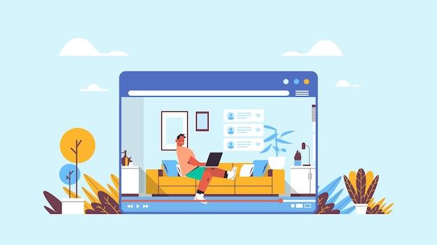 Człowiek bloger za pomocą laptopa nagrywanie wideo online blog wideo transmisja na żywo koncepcja blogowania facet vlogger w oknie przeglądarki internetowej wnętrze salonu w poziomie