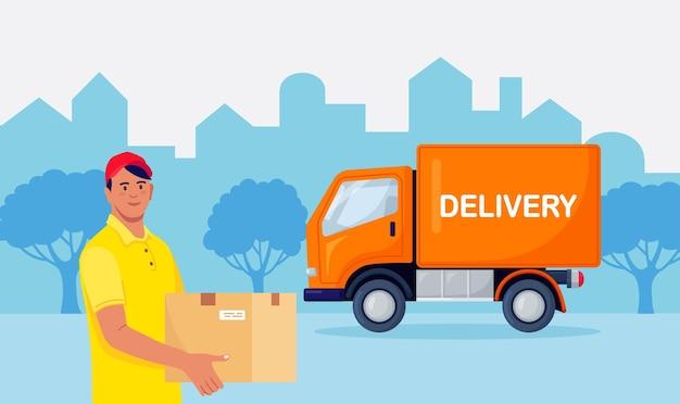 Człowiek dostawy trzymać paczkę z żółtym ciężarówką na tle. młody mężczyzna kurier w mundurze z pudełkiem w ręku. wysyłka towaru vanem