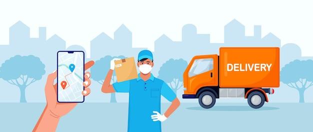 Człowiek dostawy z medycznym maski ochronnej na jego twarzy trzymając pakiet z żółtym ciężarówką na tle. dostawa w czasie kwarantanny. bezpieczne zamówienie wysyłki. aplikacja do dostarczania online na ekranie telefonu