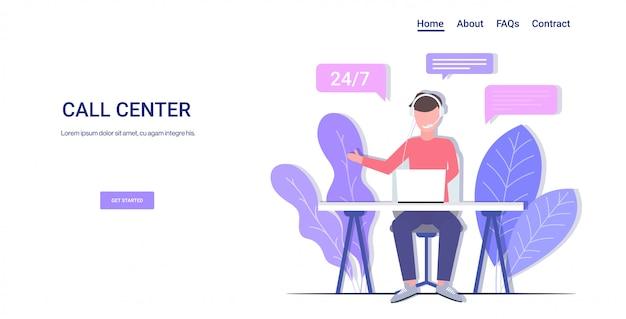Człowiek infolinia operator z zestawem słuchawkowym siedzi w miejscu pracy wsparcie techniczne klienta obsługa klienta centrum telefoniczne konsultant koncepcja odpowiedzi odpowiedzi na pełną długość poziomej kopii przestrzeni