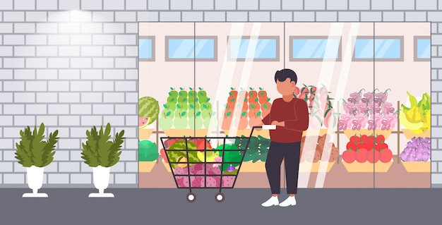 Człowiek klienta pchanie wózka wózek z artykuły spożywcze warzywa i owoce zakupy koncepcja nowoczesny sklep spożywczy supermarket zewnętrzny na zewnątrz pełnej długości poziomej