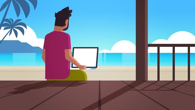 Człowiek korzysta z laptopa na tropikalnej plaży wakacje letnie komunikacja online blogowanie koncepcja bloger widok z tyłu siedzi na drewnianym tarasie pejzaż morski