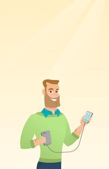 Człowiek ładujący smartfon z przenośnej baterii