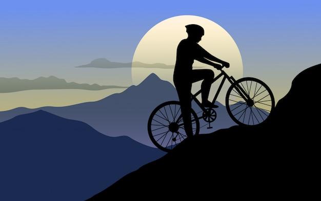 Człowiek na rowerze na wzgórzach o zachodzie słońca