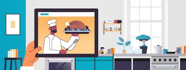 Człowiek ogląda afroamerykanin kucharz bloger żywności przygotowujący indyka na ekranie tabletu online koncepcja gotowania kuchnia wnętrze portret poziomy ilustracji