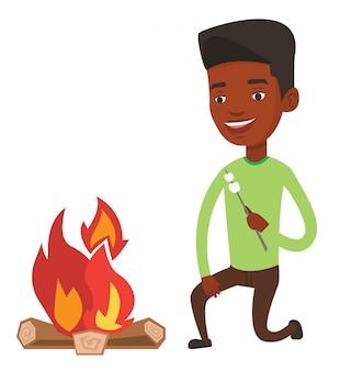 Człowiek pieczenia zefir na ognisku.