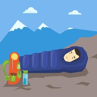 Człowiek śpi w śpiwór w górach.