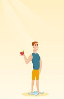 Człowiek stojący na skali i trzymając jabłko w ręku.