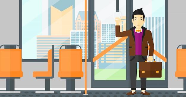 Człowiek stojący wewnątrz transportu publicznego.