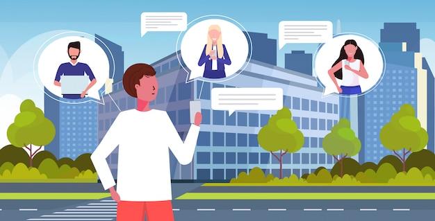 Człowiek za pomocą aplikacji mobilnej na czacie online sieci społecznościowej mowy czat bańka komunikacja koncepcja