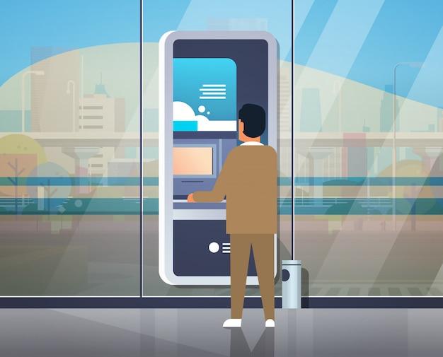 Człowiek za pomocą bankomatu samoobsługowego