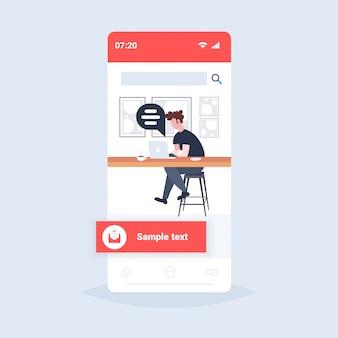 Człowiek za pomocą laptopa czat bańka social media komunikacja koncepcja facet kawiarnia gość siedzi przy biurku licznika picia kawy online mowy rozmowy smartphone ekran pełnej długości