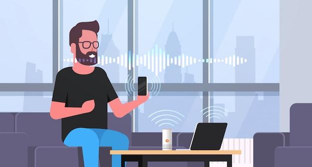 Człowiek za pomocą smartfona i laptopa kontrolowane przez inteligentne głośniki rozpoznawania głosu koncepcja nowoczesny salon wnętrze płaski poziomy portret