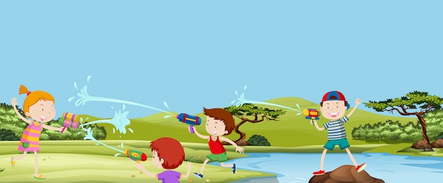 Cztery dzieci gry watergun w parku
