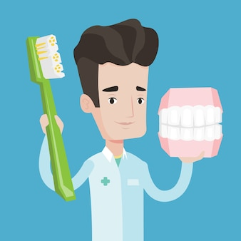 Dentysta z modelem szczęki i szczoteczką do zębów.