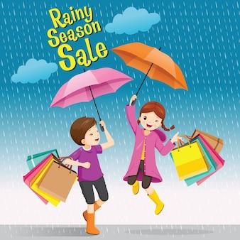 Deszczowa wyprzedaż, chłopiec i dziewczynka pod parasolem, zabawnie skaczący z wieloma torbami na zakupy