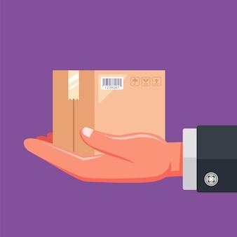 Dłoń listonosza trzyma dostarczoną przesyłkę. ilustracja wektorowa płaskie.