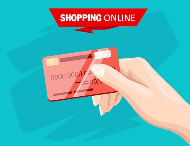 Dłoń trzymająca czerwoną kartę kredytową do płatności online i ilustracji stylu zakupów na turkusowym tle