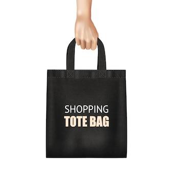 Dłoń trzymająca modną czarną płócienną torbę na zakupy