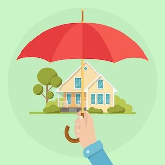 Dłoń trzymająca parasol chroniący dom jako ilustracja ubezpieczenia mienia i zdrowia