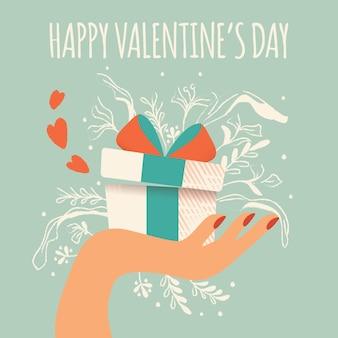 Dłoń trzymająca pudełko z sercami wychodzącymi, dekoracją i wiadomością typograficzną. kolorowe, ręcznie rysowane ilustracja na happy valentines day. kartkę z życzeniami z liśćmi i elementami dekoracyjnymi.