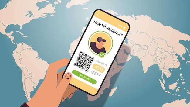 Dłoń trzymająca smartfon z cyfrowym paszportem odpornościowym z kodem qr na ekranie bez ryzyka pandemii covid-19