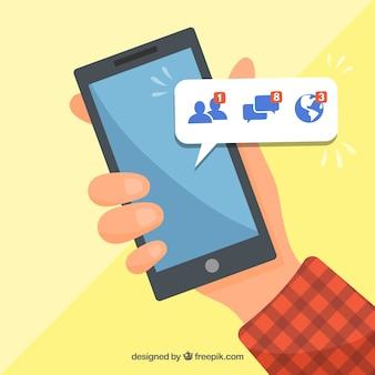 Dłoń trzymająca telefon z powiadomieniami na facebooku