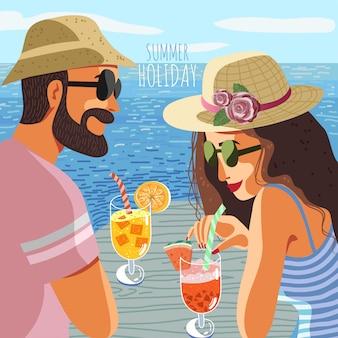 Dobiera się mężczyzna i kobiety w kapeluszach i słońc szkłach na tle błękitny denny napój pije owocowego koktajl