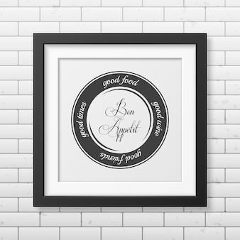 Dobre jedzenie, dobre wino, dobrzy przyjaciele, dobre czasy. smacznego. - typograficzny cytat w realistycznej kwadratowej czarnej ramce na ścianie z cegły.