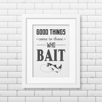 Dobre rzeczy przychodzą do tych, którzy przynęty cytuj typograficzny w realistycznej kwadratowej białej ramce na ścianie z cegły