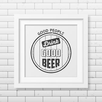 Dobrzy ludzie piją dobre piwo - typograficzny cytat w realistycznej kwadratowej białej ramce na ścianie z cegły