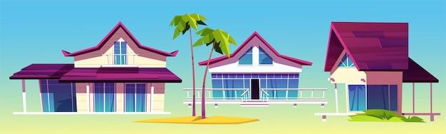 Domki letniskowe, bungalowy na plaży morskiej, architektura tropikalnego hotelu i palmy